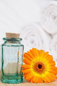 Sunflower with a glass phial and white towels — Stock Photo
