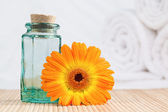 A glass phial and a sunflower with white towels — Stock Photo