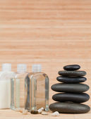 Glass flasks with pebbles and a black stones stack — Stock Photo