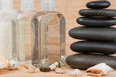 Close up of pebbles with a black pebbles stack and glass flasks — Stock Photo