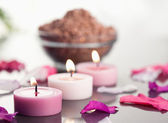 Close up of lighted candles with a brown gravel bowl and petals — Stock Photo