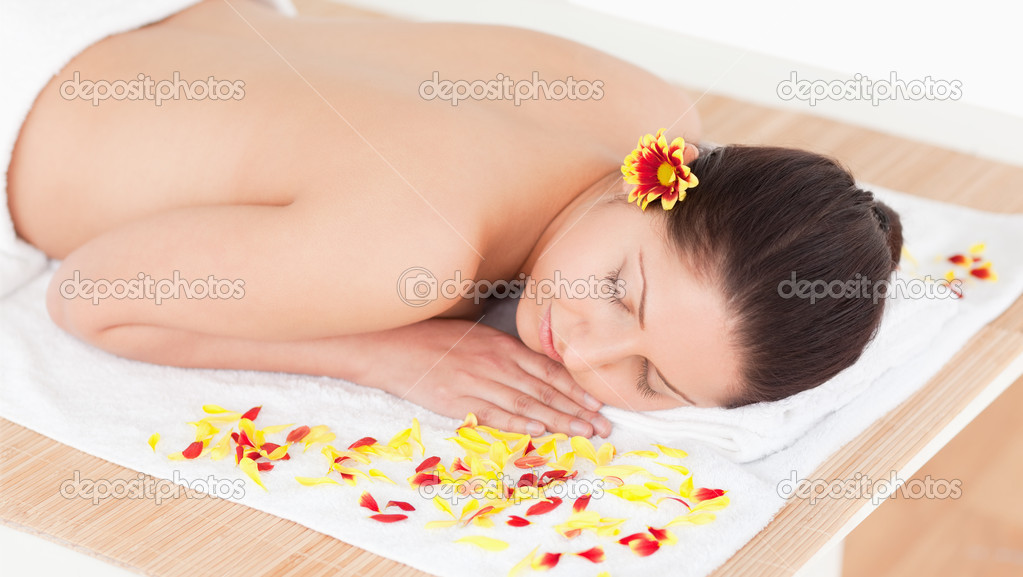 Young woman sleeping with flower petals around her and a flower on her ear — Stock Photo #10599101
