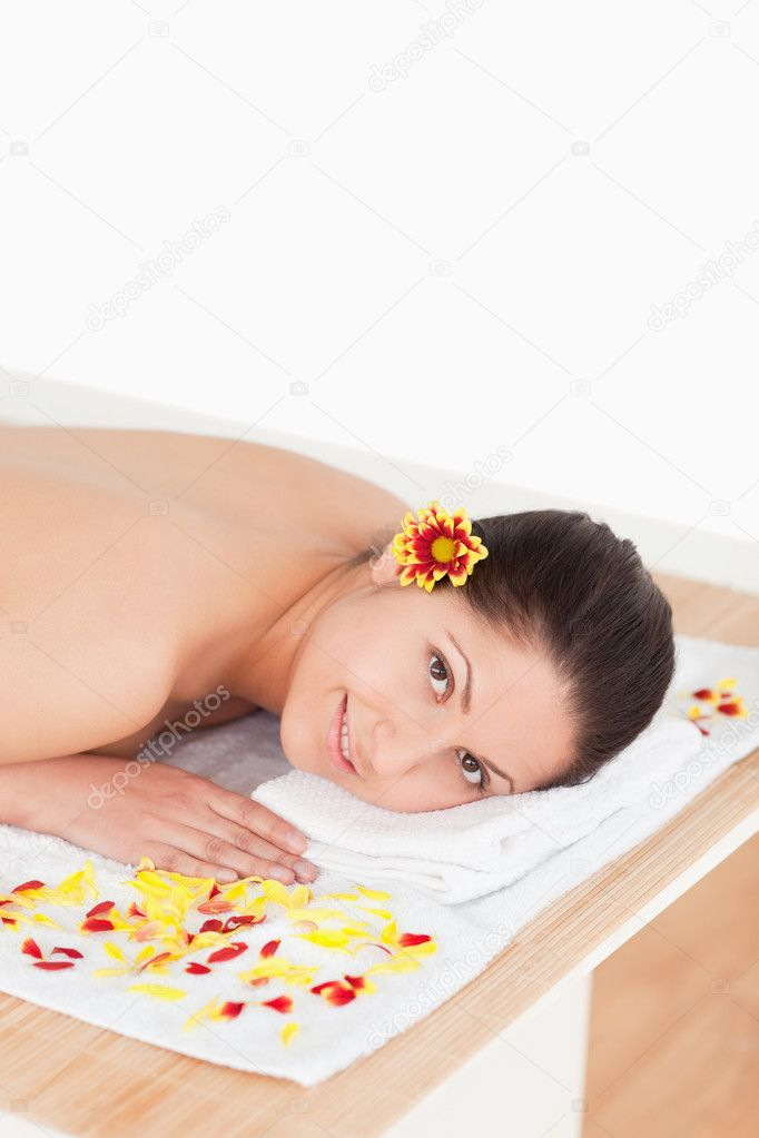 Young beautiful woman surrounded by flowers looking at the camera  Stock Photo #10599133