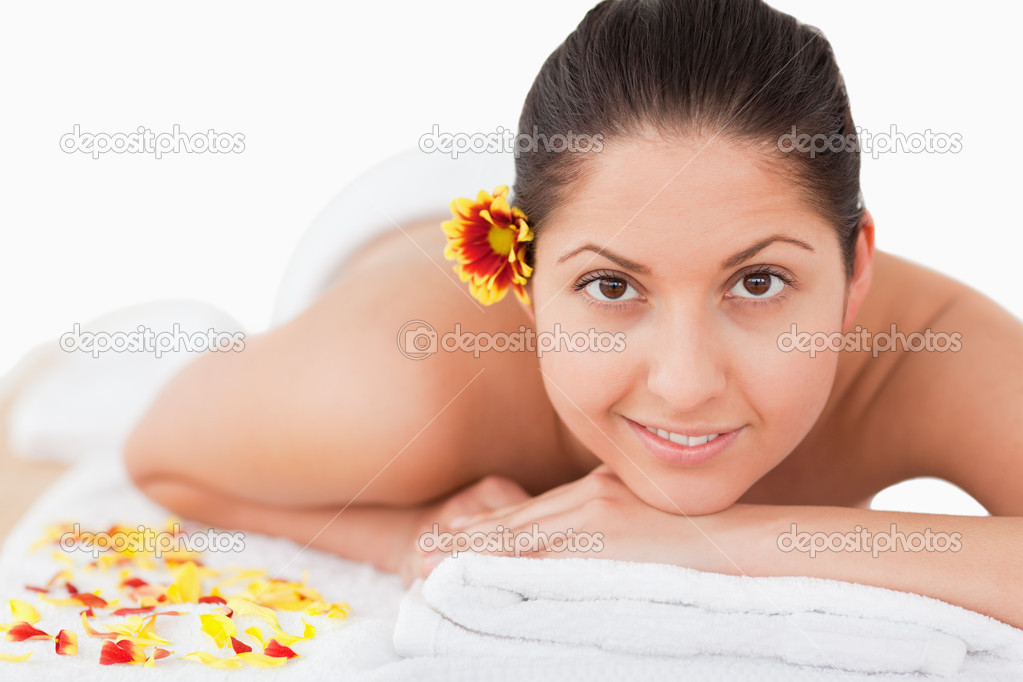 Young beautiful woman having a flower on her ear while looking at the camera in a spa — Stock Photo #10599144