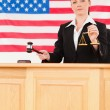 Young judge knocking a gavel and holding scales of justice — Stock Photo