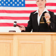 Stock Photo: Young judge knocking gavel and holding scales of justice