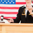 Portrait of a young judge knocking a gavel and holding scales of — Stock Photo