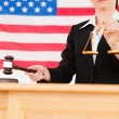 Stock Photo: Portrait of cute judge knocking gavel and holding scales of