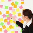 Woman putting colourful repositionable notes on a white wall - Foto Stock