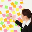 Woman putting colourful repositionable notes on a white wall - Stock Photo
