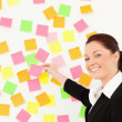 Smiling woman putting repositionable notes on a white wall — Stock Photo