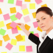 Serious woman putting repositionable notes on a white wall — Stock Photo #10601420