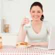 Beautiful woman relaxing on her laptop and posing while drinking — Stock Photo