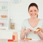 Beautiful woman preparing a slice of bread and marmalade — Stock Photo