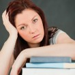 Close up of a tired student with her forearm om her books — Stock Photo