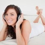 Charming female with headphones lying — Stock Photo