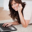 Charming brunette female on the phone while relaxing with her la — Stock Photo