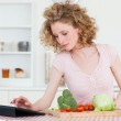 Pretty blonde woman relaxing with her tablet while cooking some — Stock Photo #10602660