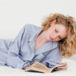 Beautiful blonde woman reading a book while lying on her bed — Stock Photo #10602742