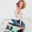 Cute blonde woman trying to close her suitcase in her bedroom — Stock Photo