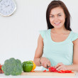 Woman slicing a pepper while looking at the camera — Stock Photo