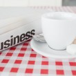 A cup of tea and a newspaper on a tablecloth — Stock Photo