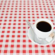 A cup of coffe on a tablecloth — Stock Photo