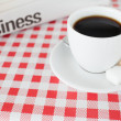 A cup of coffee and a newspaper on a tablecloth — Stockfoto