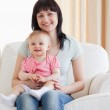 Beautiful woman holding her baby in her arms while sitting on a — Stock Photo
