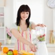 Beautiful brunette woman using a mixer while standing — Stock Photo #10603442