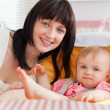 Beautiful brunette woman posing with her baby while sitting — Stock Photo