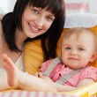 Good looking brunette woman posing with her baby while sitting — Stock Photo