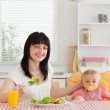 Charming brunette woman eating a salad next to her baby while si — Stock Photo #10603516