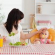 Gorgeous brunette woman eating a salad next to her baby while si — Stock Photo