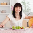 Attractive brunette woman eating a salad next to her baby while — Stock Photo