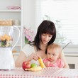Cute brunette woman showing a banana to her baby while sitting — Stock Photo