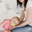 Attractive brunette female posing with her baby lying on her — Stock Photo #10603620