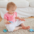 Royalty-Free Stock Photo: Baby playing with puzzle pieces while sitting on a carpet