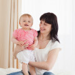 Cute brunette woman holding her baby on her knees while sitting — Stock Photo