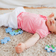 Cute blond baby playing with puzzle pieces while lying on a carp — Stock Photo #10603667