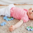 Cute blond baby playing with puzzle pieces while lying on carp — Stock Photo #10603667