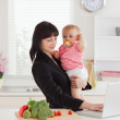 Beautiful brunette woman in suit holding her baby in her arms wh — Stock Photo #10603750