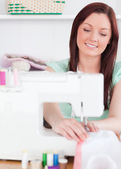 Good looking red-haired woman using a sewing machine in the livi — Stock Photo