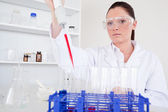 Beautiful female biologist holding a manual pipette with sample — Stock Photo