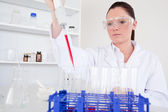 Attractive female biologist holding a manual pipette with sample — Stock Photo