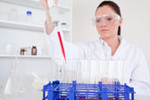 Pretty female biologist holding a manual pipette with sample fro — Stock Photo