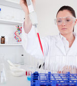 Gorgeous female biologist holding a manual pipette with sample f — Stock Photo