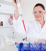 Cute female biologist holding a manual pipette with sample from — Stock Photo