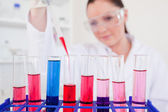 Attractive red-haired scientist filling up a test tube — Stock Photo