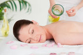 Masseuse versing massage oil on a beautiful woman's back in a sp — Stock Photo